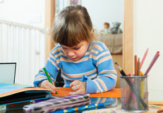 Serious child drawing on paper in home Stock Photo