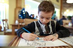 Serious child drawing in restaurant. Serious child drawing at table in a restaurant royalty free stock photo