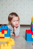 Serious Child girl lying near bright plastic construction blocks. Toddler playing on the floor. Developing toys. Early learning. Stock Photos