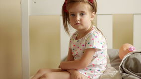 Serious child looking at camera sits on bed. Behind her is her doll. Favorite toy. Close-up portrait stock footage