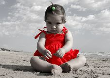 Serious child with a red dress. Serious child plying with the sand with a red dress on b/w background Royalty Free Stock Images