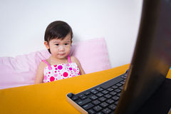 Serious child sitting and looking a story on digital tablet comp Royalty Free Stock Image