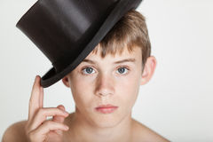 Serious child tipping his hat on head Royalty Free Stock Photos