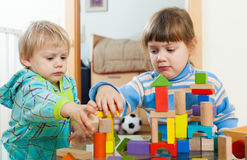 Serious children playing with wooden blocks Royalty Free Stock Photos