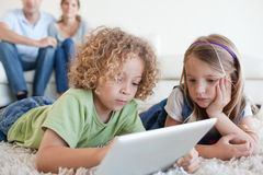 Serious children using a tablet computer while their happy paren Stock Image
