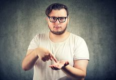 Serious chubby man asking for more money to pay back debt. Young serious chubby man asking for more money to pay back debt stock photo