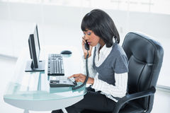 Serious classy businesswoman answering the phone Royalty Free Stock Images