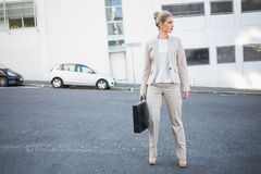 Serious classy businesswoman holding briefcase posing Royalty Free Stock Image