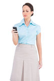 Serious classy young businesswoman sending text message Stock Image