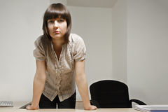 Serious clerk. Serious young caucasian brunette female clerk standing at desk Stock Image