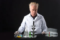 Serious clinician studies in laboratory and looking at flask and bubble. Royalty Free Stock Photography