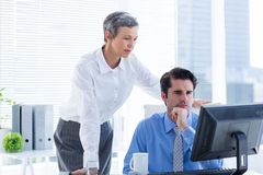 Serious colleagues working together on computer Royalty Free Stock Photos