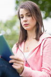 Serious college girl using tablet PC outdoors Royalty Free Stock Photo