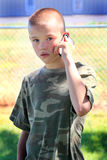 Serious Communication. A cute teenaged boy with short hair wearing a camo shirt talking seriously on the phone.  Shallow depth of field Stock Photography