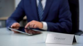 Serious company director using tablet pc on workplace, checking important files royalty free stock photos