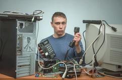 Computer repairman. Computer technician engineer. Support service. Serious Computer technician is consulting a users by their questions by the phone. PC repair Stock Images