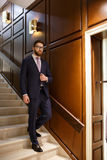 Serious concentrated bearded young businessman on ladder Royalty Free Stock Image