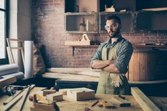 Serious concentrated confident qualified handsome bearded cabinet-maker wearing apron and safety glasses is standing with crossed stock image