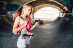 Serious and concentrated girl is standing and holding phone in hand. Also she is holding rollers hanging over shoulder stock photography