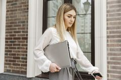Serious and concentrated girl is walking down the street outside. She is holding laptop. Girl is looking down. She is thoughtful royalty free stock photography