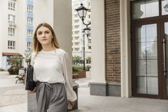 Serious and concentrated girl is walking down the street outside. She is holding laptop. Girl is looking up. She is thoughtful.  royalty free stock images