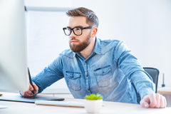 Serious concentrated man designer drawing with graphic pen tablet Stock Image