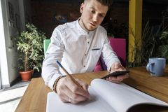 Serious and concentrated man is sitting at table and looking on the notepad. He is holding pen in other hand. There is a journal.  royalty free stock photo