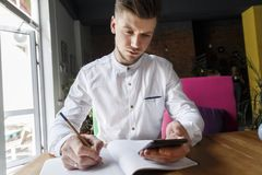 Serious and concentrated man is sitting at table and looking on the phone. He is holding pen in other hand. There is a journal. Lying on table Man is sitting royalty free stock images