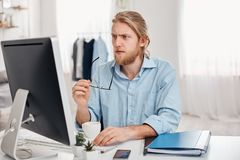 Serious concentrated pensive male businessman in blue shirt holds spectacles in hand, works on computer, thinks about stock photo