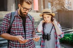 Serious and concentrated tourists stand at steps. He holds tablet in hands. They both look at it. Young woman hold lace stock photography