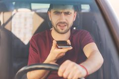 Serious concentrated unshaven brunet male drives car, makes voice call, speaks with colleague, goes for work, stands in traffic ja. M, being busy. Handsome man Royalty Free Stock Image