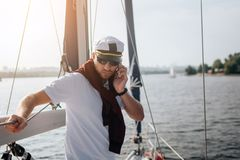 Serious and concentrated yachtsman stands and lean on railing. He hold phone in hand and look down. Guy works. Itis. Sunset outside stock image