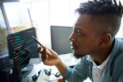Learning coding language himself. Serious concentrated young African-American programmer looking confused while learning coding language himself stock photo