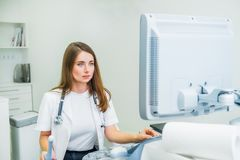Serious, concentrated young doctor, specialist using Ultrasound Scanning Machine for pacient testing. Copy space. Selective focus.  royalty free stock image