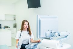 Serious, concentrated young doctor, specialist using Ultrasound Scanning Machine for pacient testing. Copy space. Selective focus.  royalty free stock photo