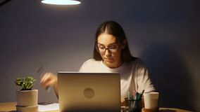 Serious young student studying using pc laptop, woman working late stock footage