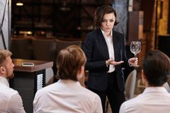 Confident restaurant manager reporting waiters. Serious confident attractive young female restaurant manager in formal suit standing in front of waiting staff stock images