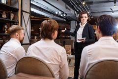 Restaurant manager explaining tasks to waiters. Serious confident attractive young female restaurant manager with short hair standing in front of waiters and royalty free stock image
