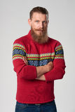 Serious confident bearded hipster man. In woolen sweater standing with folded hands and looking at camera, studio portrait over grey background Stock Photos