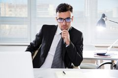 Serious confident businessman working in office. Sitting at desk, looking at camera Stock Photography