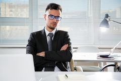 Serious confident businessman working in office. Sitting at desk, looking at camera Royalty Free Stock Photo