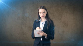 Serious confident businesswoman writing in her organizer  on studio background. Royalty Free Stock Photo