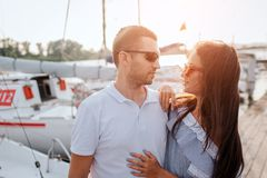 Serious and confident couple stands on pier and look at each other. They wear sunglasses. People stand very close. She stock photography