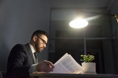 Concentrated bearded businessman in glasses working with documen stock image