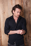 Serious confident man in black shirt standing and looking away Royalty Free Stock Photo