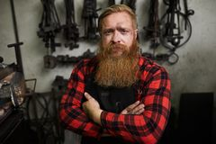 Serious confident smith with long beard. Portrait of serious confident handsome male smith with long beard looking scowling and crossing arms on chest in stock images