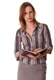 Serious confident young woman teacher with textboo. Serious confident young woman teacher holds textbook in her hands on white background Royalty Free Stock Image