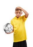 Serious, confused boy with a soccer ball holding his head isolated on a white background. School activities concept. Royalty Free Stock Image