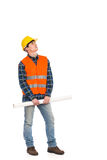 Serious construction worker holding rolled paper plan and looking up. Royalty Free Stock Images