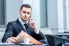 Serious conversation. Businessman sitting at a laptop and mobile Stock Image